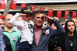 Antalya'da jandarma su altı kurtarma ekibinin dalış eğitiminde rahatsızlanarak şehit olan Jandarma Astsubay Kıdemli Üst Çavuş Mesut Akmeşe, İzmir'in Dikili ilçesinde son yolculuğuna uğurlandı. Çarşı Cami'ne getirilen şehidin naaşını, kızı 8 yaşındaki Hayriye Nil (solda) ve eşi Latife Akmeşe (sağda) asker selamıyla karşıladı.  ( Metin Aydemir - Anadolu Ajansı )