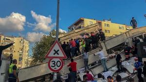 Merkez üssü Ege Denizi'nin Seferihisar ilçesi açıkları olan 6,6 büyüklüğündeki deprem nedeniyle İzmir'in Bayraklı ilçesinde yıkılan binanın enkazından yaralılar çıkarıldı.  ( Tezcan Ekizler - Anadolu Ajansı )