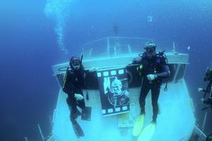 """Türkiye'nin ilk su altı fotoğraf sanatçılarından Mustafa Kapkın'ın 63 yıl önce çektiği karelerden oluşan """"Sünger Dalgıçları"""" sergisi, Çeşme açıklarında 30 metre derinlikteki askeri teknenin içinde dalış meraklılarını ve sanatseverleri bekliyor. Çeşme açıklarında Eşek Adası yakınında batırılan Sahil Güvenlik botu TCSG 68, ender görülen sanat etkinliklerinden birine ev sahipliği yapıyor. Kendi geliştirdiği cihazla 63 yıl önce Bodrum'da süngercileri fotoğraflayan Kapkın'ın kareleri, Çeşme'de yine su altında sergilenmeye başlandı. Dalış turizmini canlandırmak için batırılan ve 30 metre derinlikteki TCSG 68'de açılan """"Sünger Dalgıçları"""" isimli sergi, su altı fotoğraf sanatçıları Tahsin Ceylan, Ateş Evirgen, Lütfü Tanrıöver ve Anadolu Ajansı ekibi tarafından görüntülendi.  ( Tahsin Ceylan - Anadolu Ajansı )"""