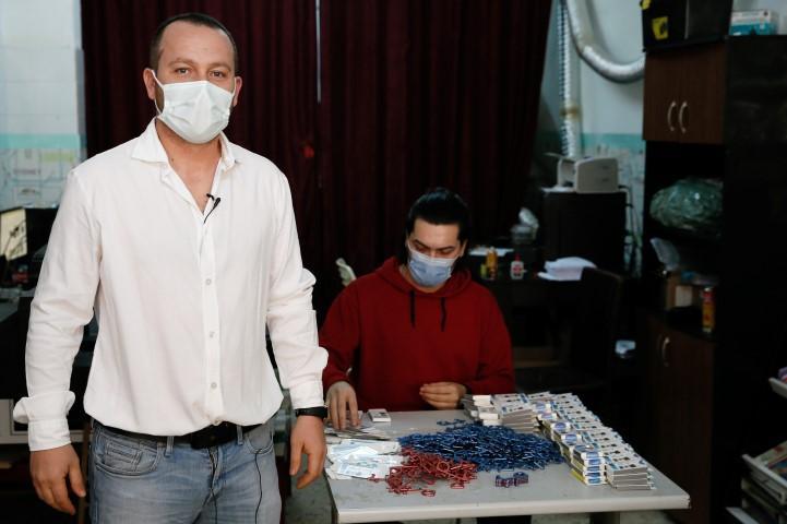 """İzmir'de bir firmanın dış mekanlarda teması azaltmak amacıyla geliştirdiği """"korona kancası"""" Avrupa ülkelerine satılıyor. Dikili ilçesinde KOSGEB desteğiyle hediyelik eşya üretmek üzere şirket kuran Gökhan Kocakuş (önde), yeni tip koronavirüs (Kovid-19) salgını sonrası turizmde görülen daralma nedeniyle alternatif faaliyet alanlarına yöneldi.   ( Ömer Evren Atalay - Anadolu Ajansı )"""