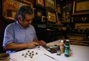 İzmirli minyatür ustası Arya Kamalı sanatını tespit tanelerine yansıtıyor. Kamalı'nın büyüteç yardımıyla ortalama 15 milimetre çapındaki tespih tanelerine çizdiği padişahların resimleri ve tuğraları, meraklılarından büyük ilgi görüyor.  ( Evren Atalay - Anadolu Ajansı )