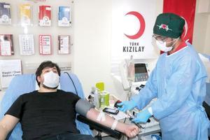 """İzmir'de yeni tip koronavirüs (Kovid-19) tedavisi tamamlanan doktor Burak Silahlı (solda), göreve döndükten sonra yoğun bakımda Kovid-19 tedavisi gören genç hastalardan etkilenerek """"immün plazma"""" bağışçısı oldu. ( Tezcan Ekizler - Anadolu Ajansı )"""